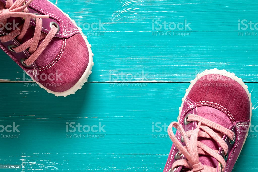 Pink baby shoes on turquoise table stock photo