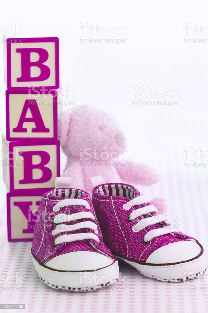 Pink baby shoes with building blocks spelling out baby stock photo