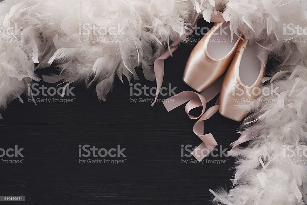 Pink ballet pointe shoes and feather on black wood background stock photo