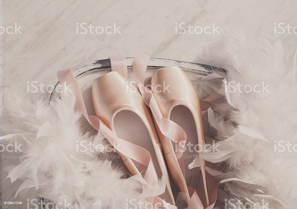 Pink ballet pointe shoes and feather on white wood background stock photo