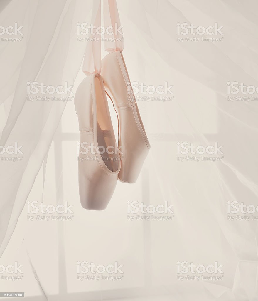 Pink ballet pointe shoes hanging on window stock photo