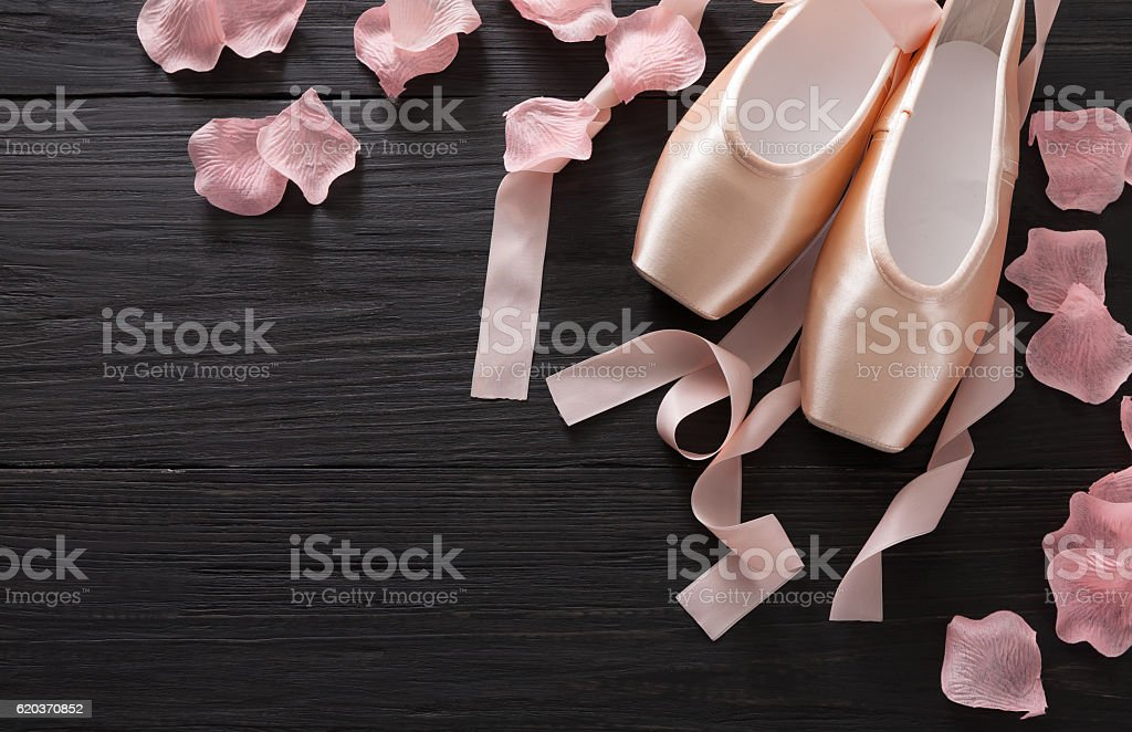 Pink ballet pointe shoes on black wood background stock photo