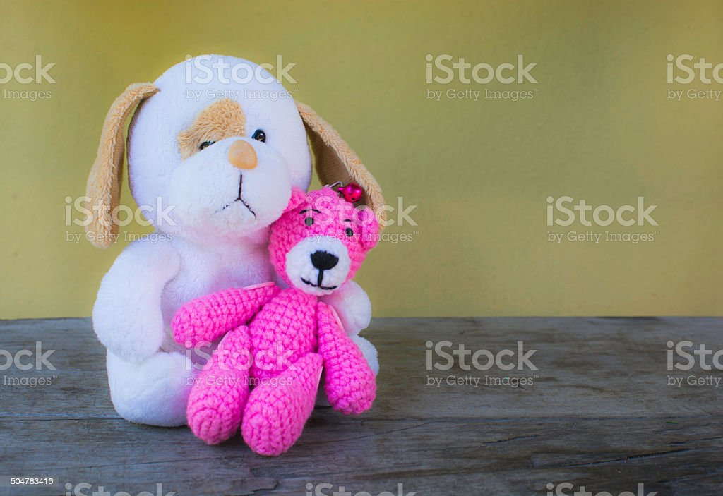 Pink bear doll sitting on White dog doll/toy and royalty-free stock photo
