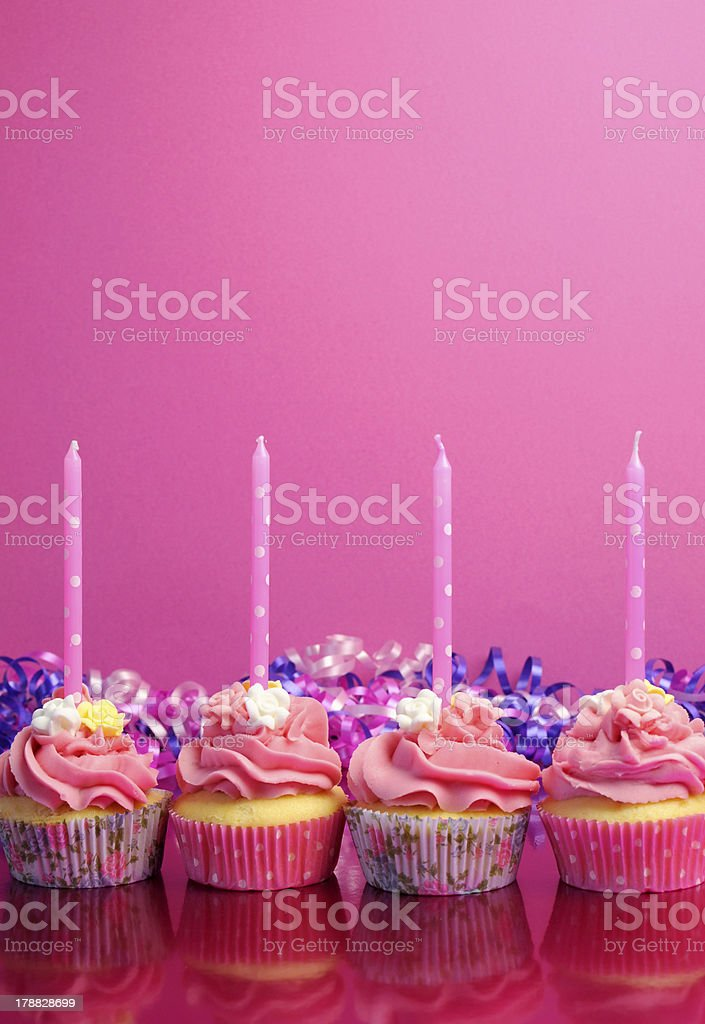 Pink birthday cupcakes with polka dot candles - vertical. royalty-free stock photo