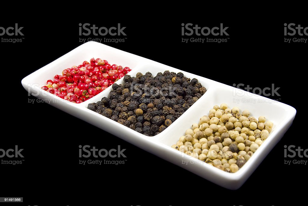 Pink, black and white peppercorns in a white dish royalty-free stock photo
