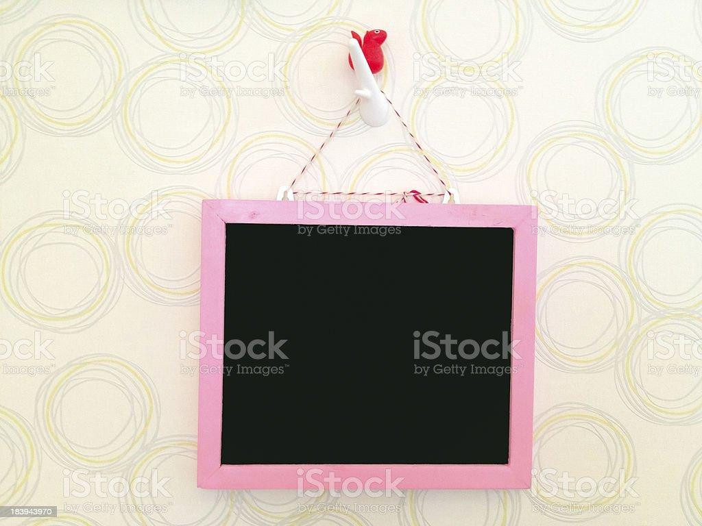 Розовый blackboard висит на стене Стоковые фото Стоковая фотография