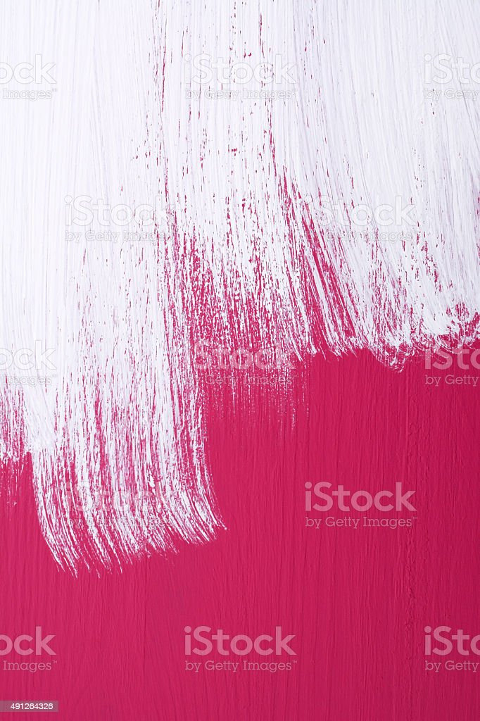 Pink board being roughly painted with white paint stock photo