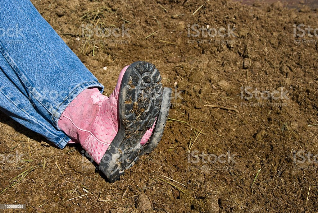 Pink Boots and Manure Pile, Farm Worker Taking a Break royalty-free stock photo