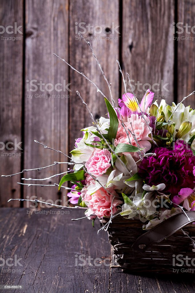 Pink bouquet from gillyflowers and alstroemeria in the basket on stock photo