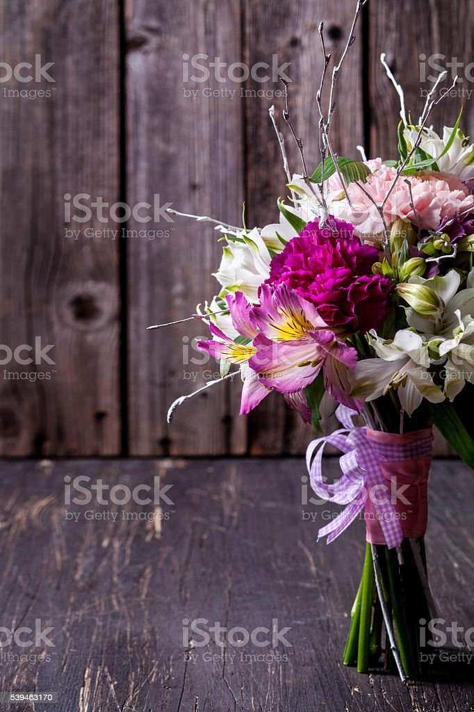 Pink bouquet from gillyflowers and alstroemeria on old, rustic w stock photo