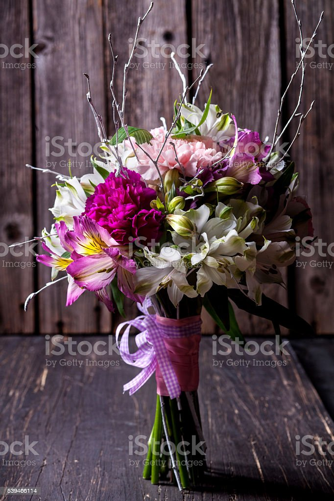Pink bouquet from gillyflowers and alstroemeria on old wooden ba stock photo