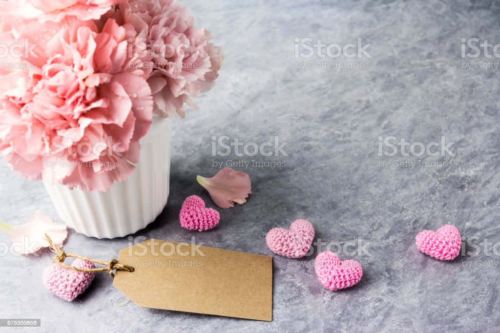 Pink carnation flower in white cup with blank brown paper tag and heart stock photo