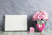Pink carnation flower in zinc bucket and blank canvas frame