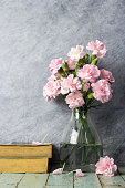 Pink carnation flowers in clear bottle and old book