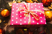 Pink Christmas gift with golden balls close-up