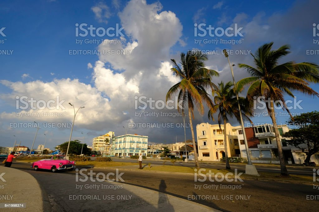 Pink classic car convertible on sunny road with palm trees in Cuba stock photo