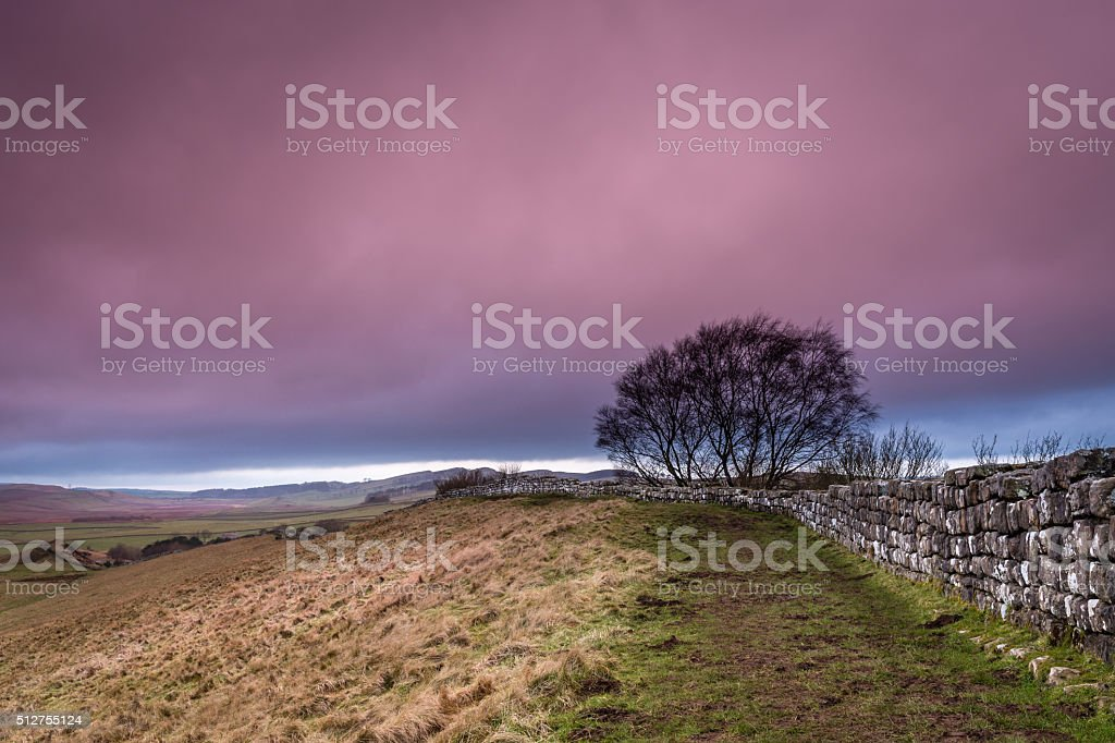 Pink cloud above Hadrian's Wall stock photo