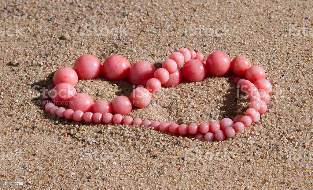 Pink coral beads lie on the sand stock photo