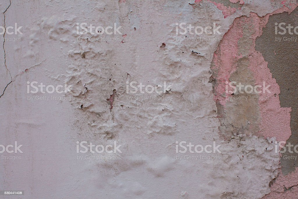 pink, cracked paint on old wall crumbling houses stock photo