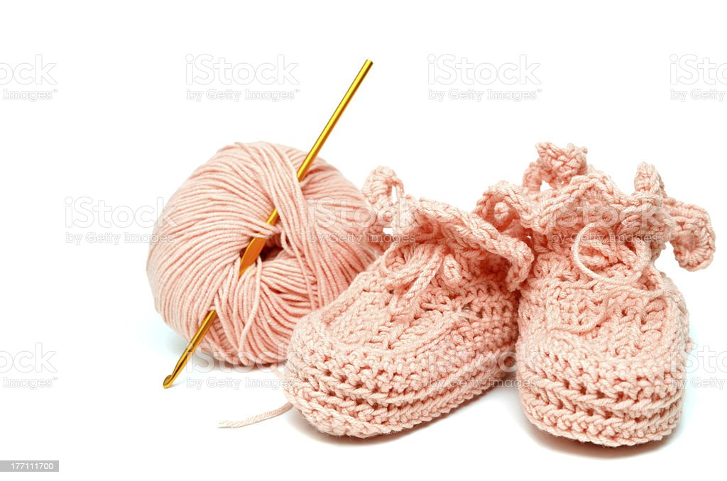 pink crocheted babby's bootees and thread with crochet royalty-free stock photo