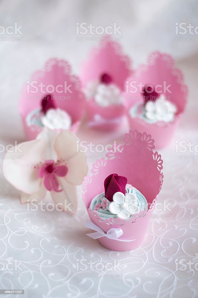 pink cupcakes decorated with cream and roses stock photo