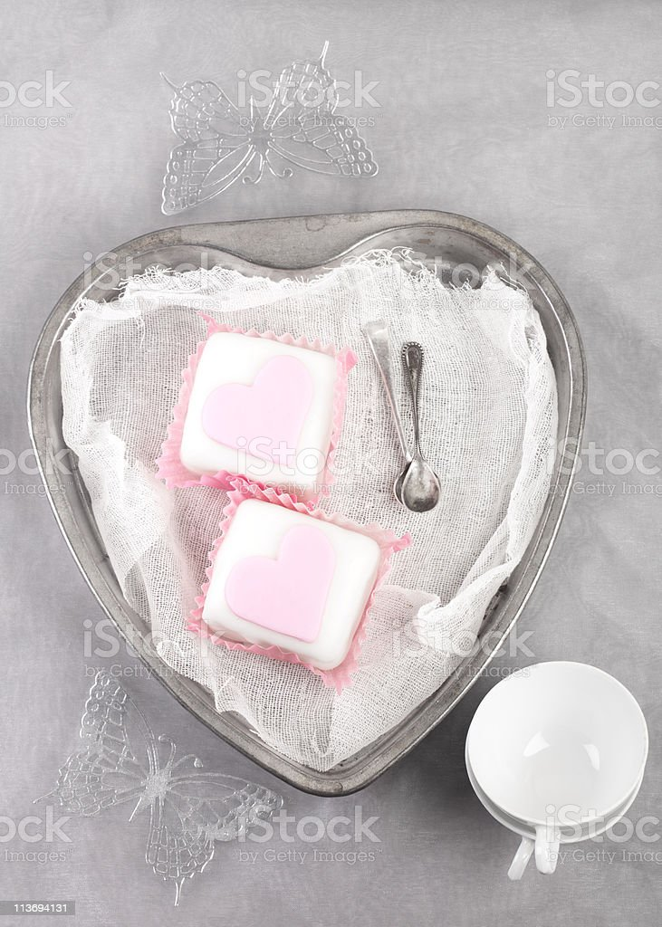 pink cupcakes in heart shaped tin with spoons and cup royalty-free stock photo