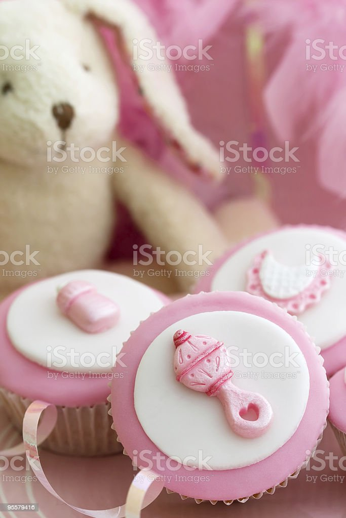 Pink decorated cupcakes and stuffed rabbit for a baby shower royalty-free stock photo
