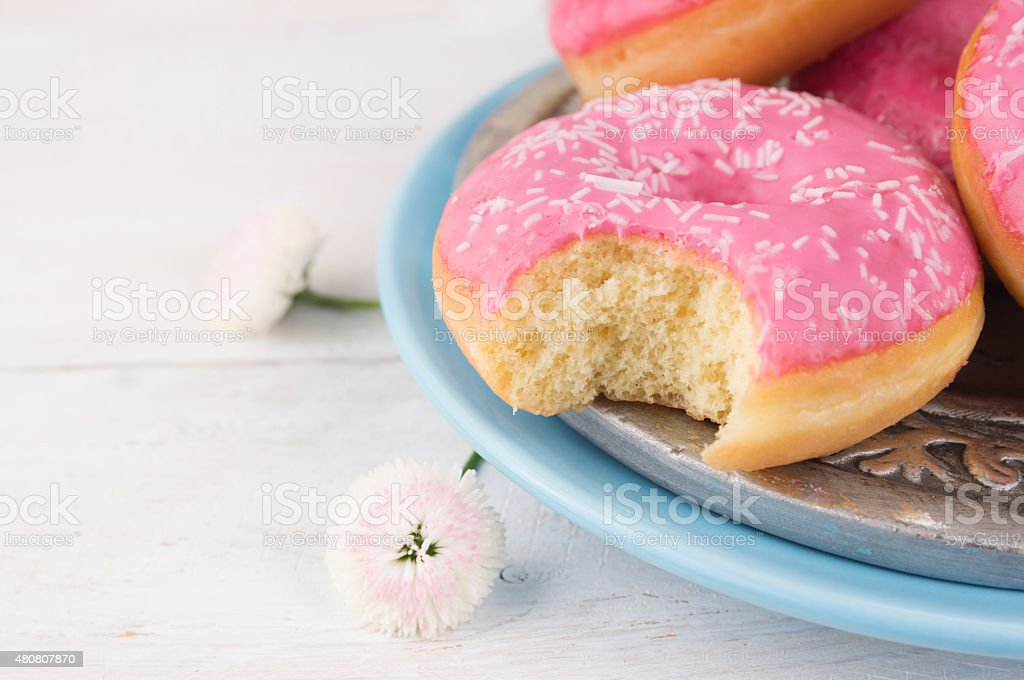 pink donut  bite off on blue palte stock photo
