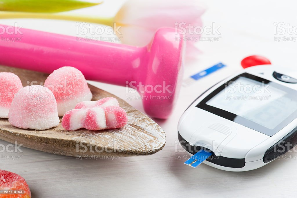 Pink dumbbell, sweets and glucose meter stock photo