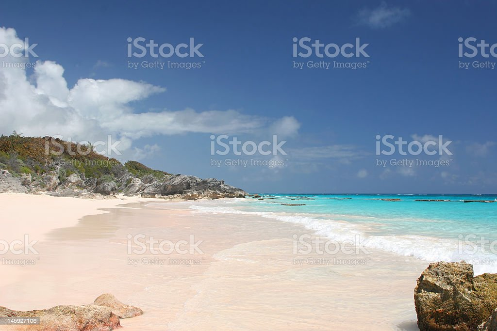 Pink empty beach with clear blue water stock photo
