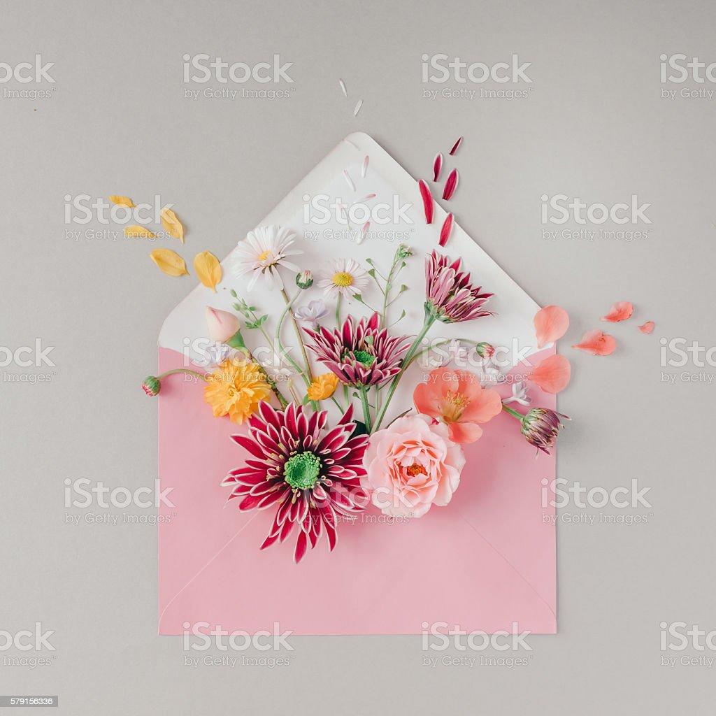 Pink envelope full of various flowers stock photo