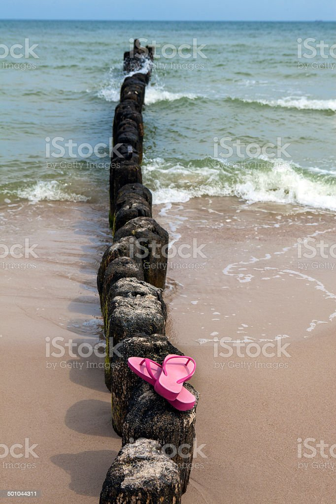 Pink flip flops on beach stock photo