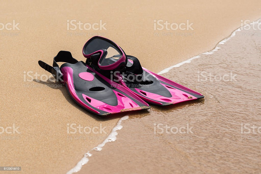 Pink flippers on the sand of beach with wave on background stock photo