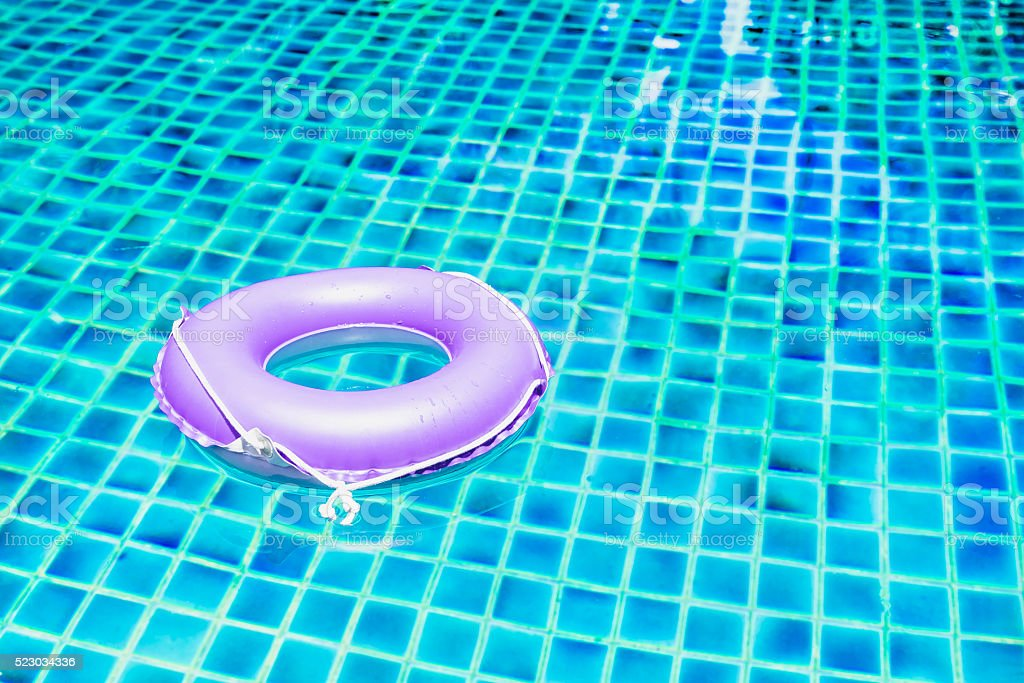 pink floating ring on blue water swimpool with waves reflecting stock photo