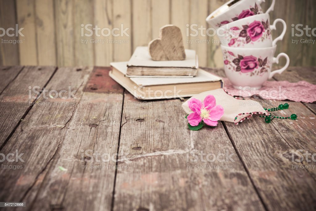 Pink Flower, old books, tea cups on rustic wooden table stock photo