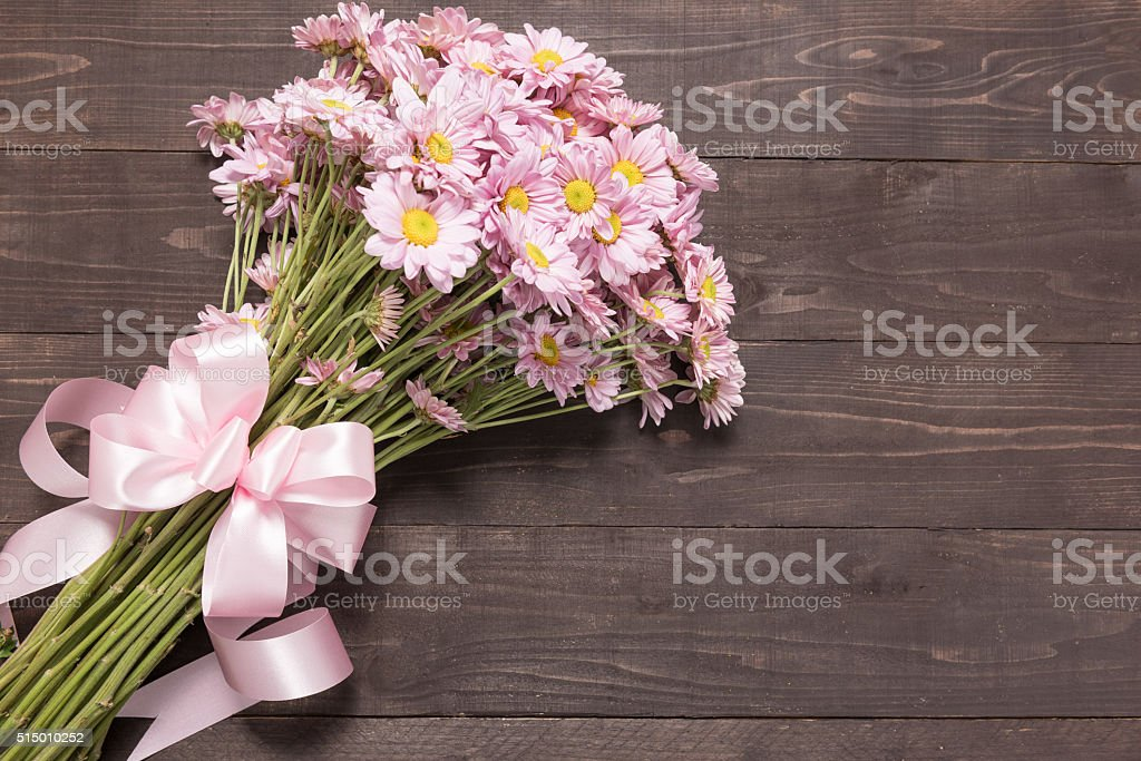 Pink flowers are on the wooden background with ribbon. stock photo