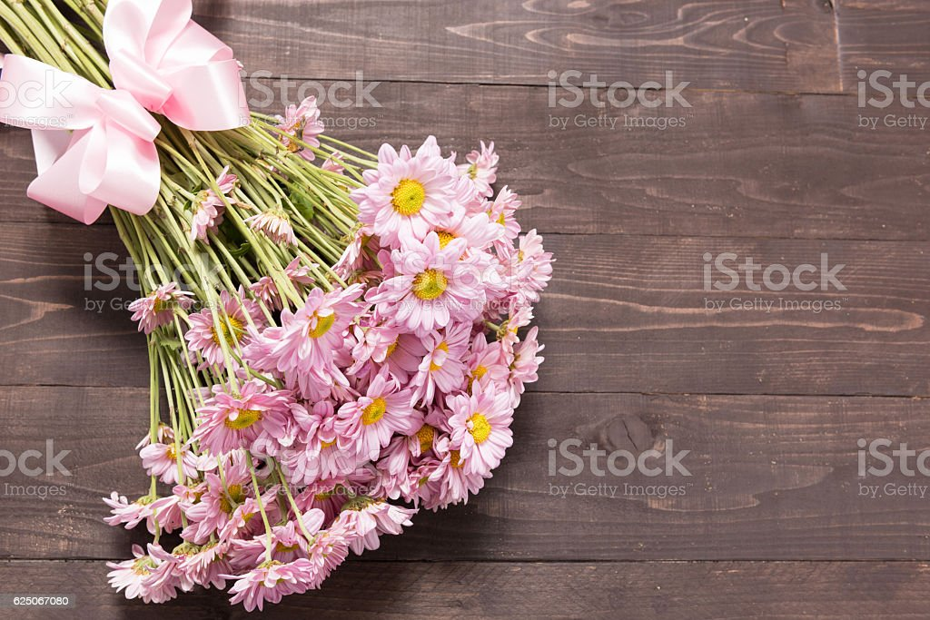 Pink flowers are on the wooden background with ribbon stock photo