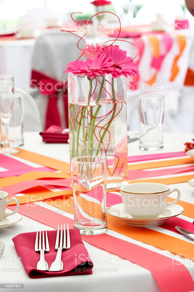 Pink flowers in a glass vase on a set dining table royalty-free stock photo