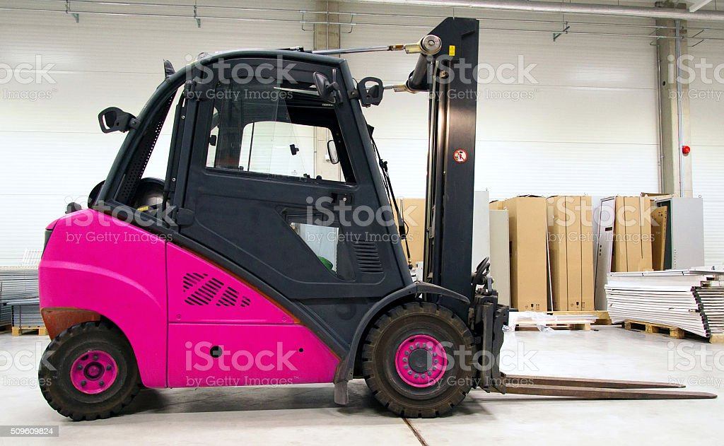Pink forklift loader in the large modern warehouse. stock photo