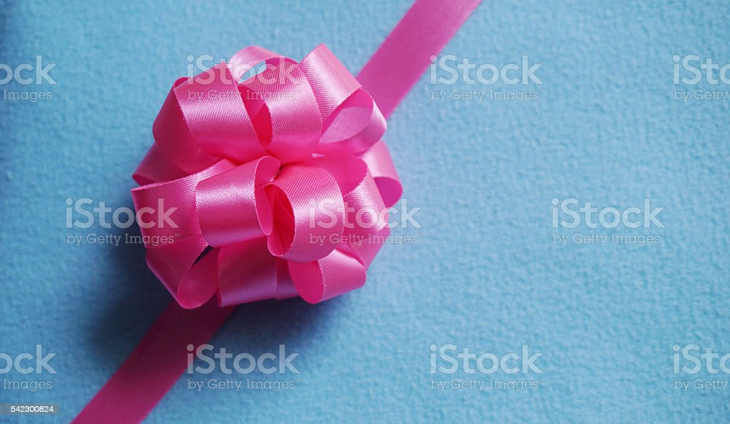 Pink gift bow on blue fabric background stock photo
