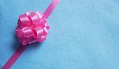 Pink gift bow on blue fabric background