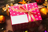 Pink gift box with blank card under Christmas tree