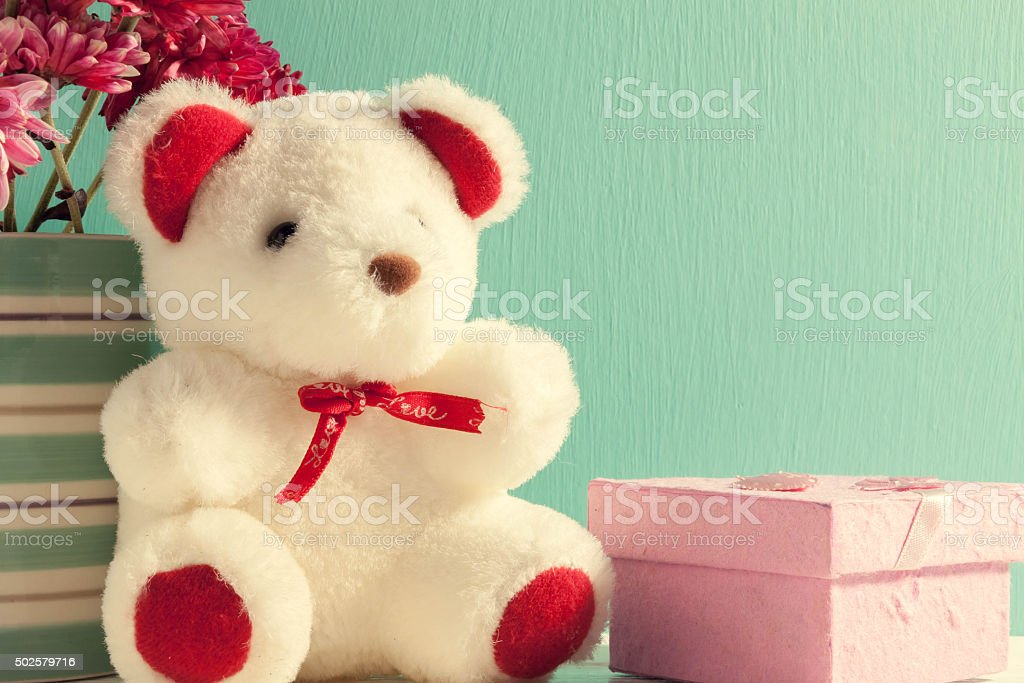 pink gift,teddy bear,flower in vase on green background. stock photo