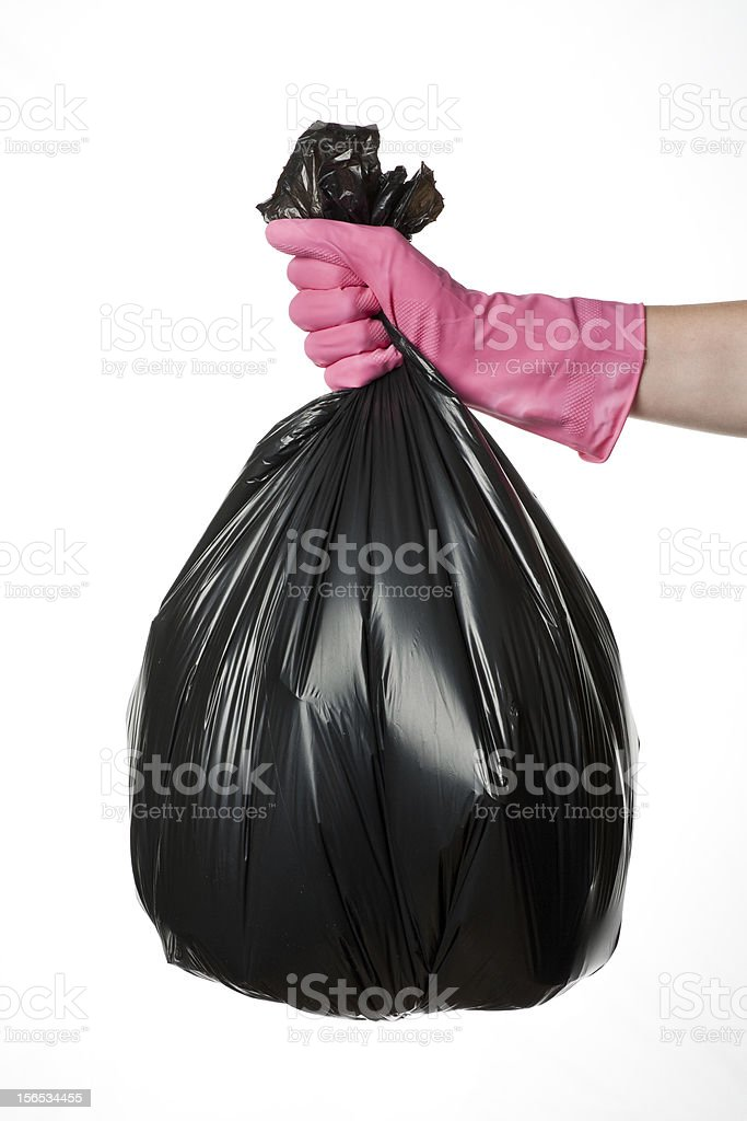 A pink gloved hand holding a rubbish bag stock photo