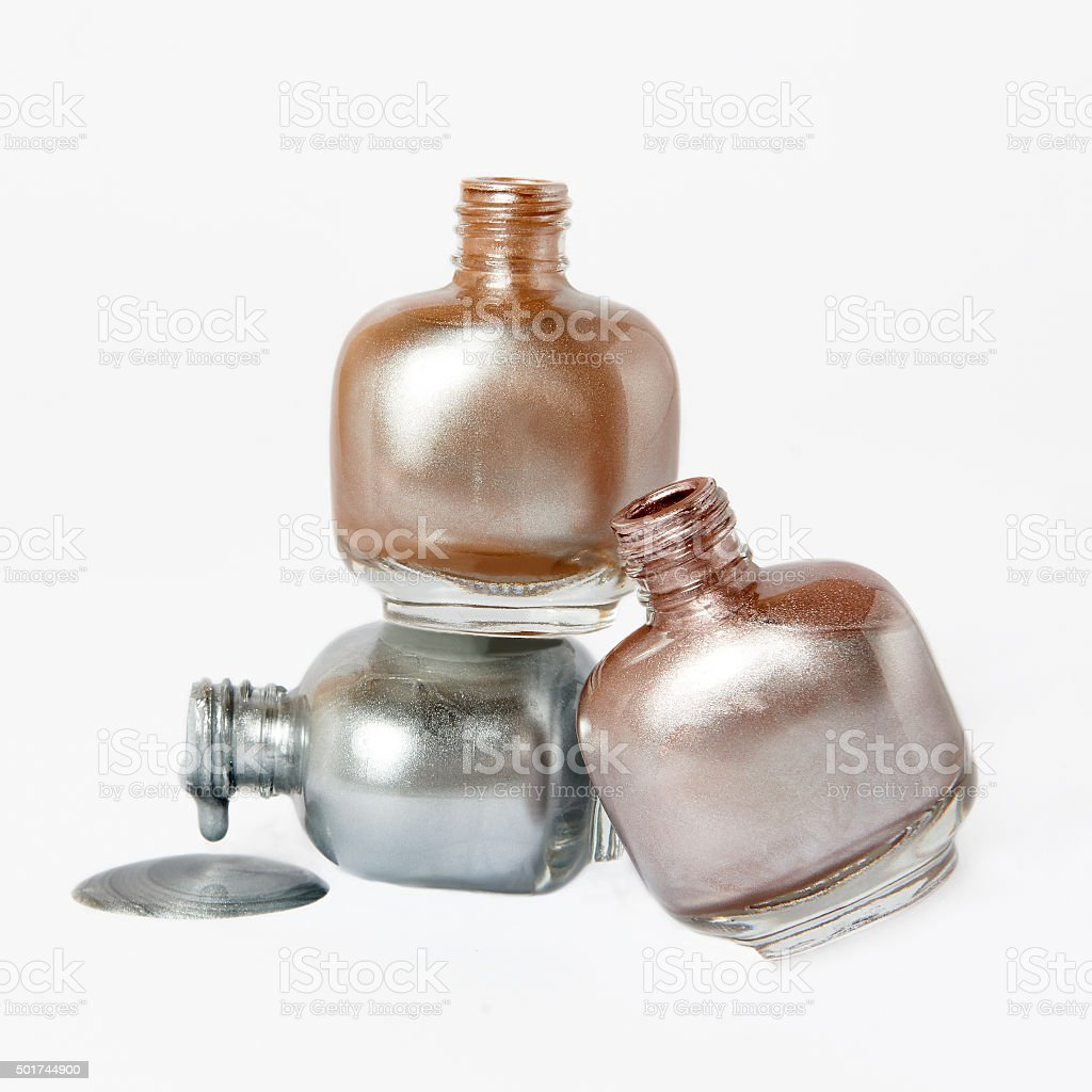 pink gold and silver nail polish bottles on white background stock photo