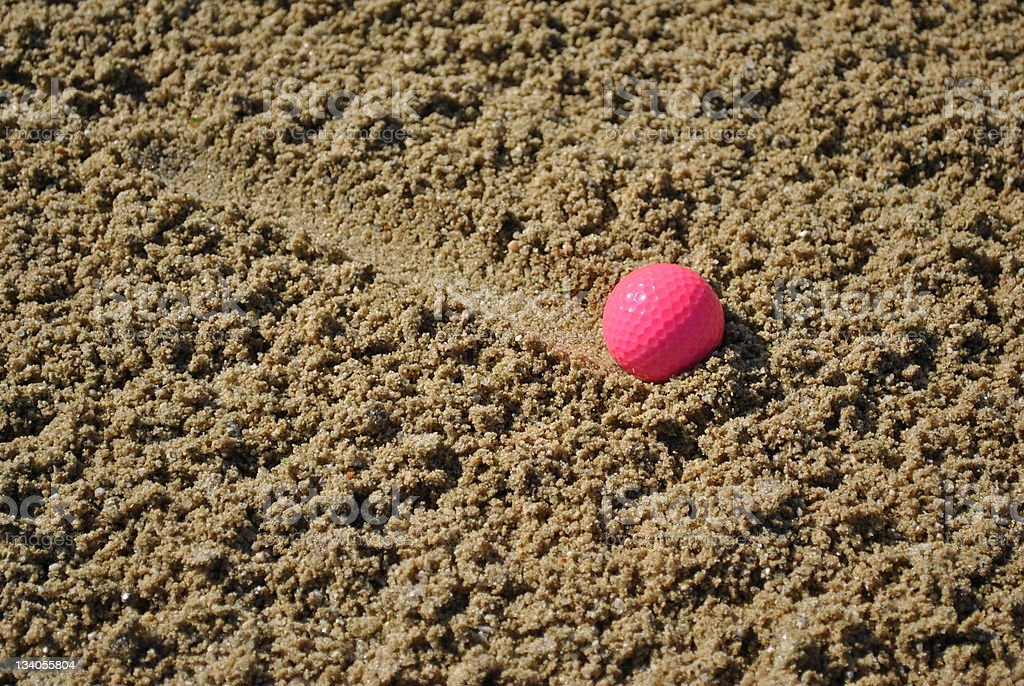 pink golf ball in a sand trap royalty-free stock photo