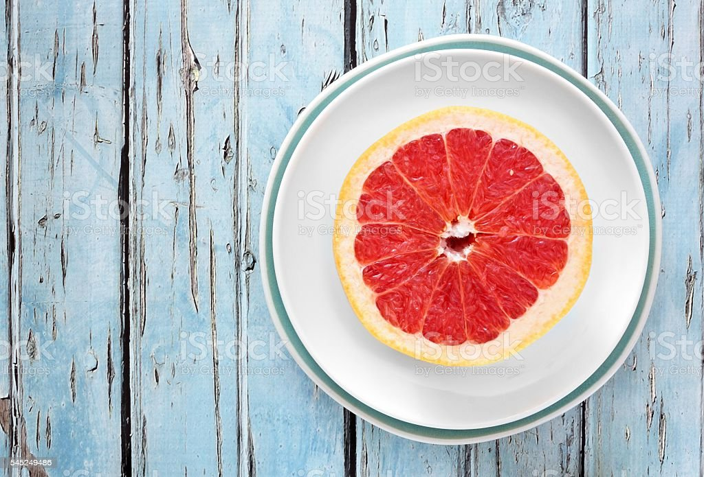 Pink grapefruit half with rustic blue wood background stock photo