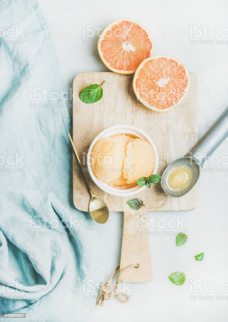 Pink grapefruit sorbet with fresh mint leaves on wooden board stock photo
