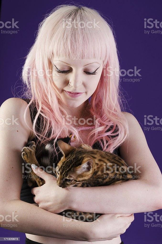Pink haired model cuddling Bengal kitten. royalty-free stock photo