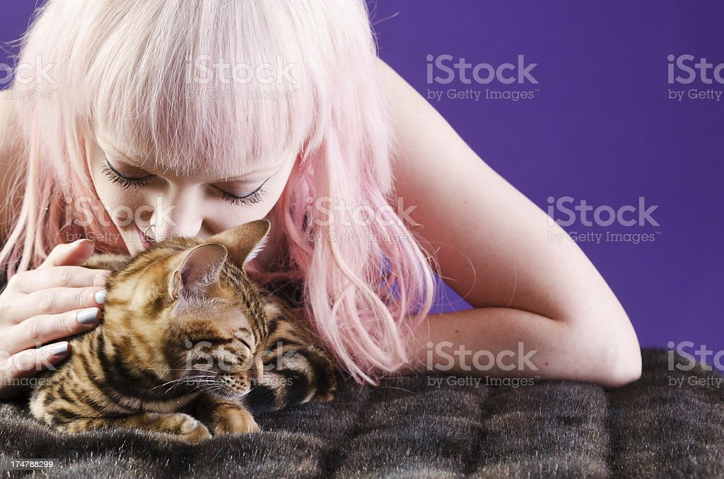 Pink haired young woman nose touching sleeping kitten stock photo